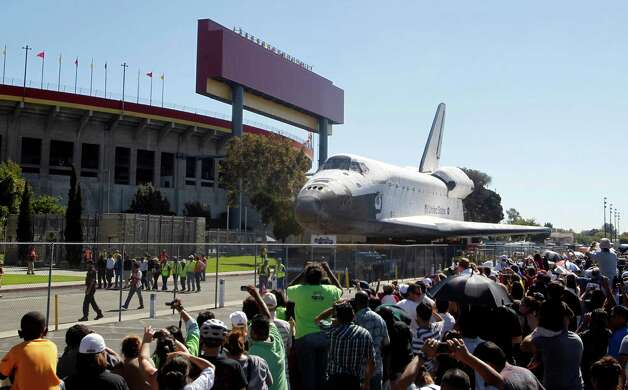 The space shuttle Endeavour moves north on Bill Robertson Lane in front of the Coliseum in Los Angeles Sunday, Oct. 14, 2012. In thousands of Earth orbits, the space shuttle Endeavour traveled 123 million miles. But the last few miles of its final journey are proving hard to get through. Endeavour's 12-mile crawl across Los Angeles to the California Science Museum hit repeated delays Saturday, leaving expectant crowds along city streets and at the destination slowly dwindling. Officials estimated the shuttle, originally expected to finish the trip early Saturday evening, would not arrive until later Sunday. Photo: AP