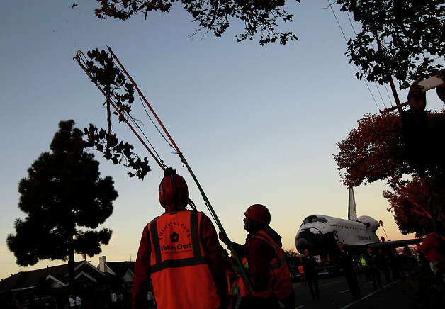 Workers trim the trees as the space shuttle Endeavour makes it's way along Martin Luther King Boulevard on Sunday, Oct. 14, 2012 in Los Angeles.  In thousands of Earth orbits, the space shuttle Endeavour traveled 123 million miles. But the last few miles of its final journey are proving hard to get through. Endeavour's 12-mile crawl across Los Angeles to the California Science Museum hit repeated delays Saturday, leaving expectant crowds along city streets and at the destination slowly dwindling. Officials estimated the shuttle, originally expected to finish the trip early Saturday evening, would not arrive until later Sunday. Photo: AP