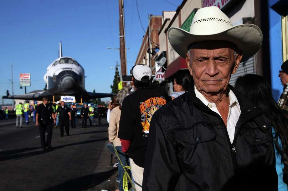 Federico Gonzales waits with spectators as the shuttle Endeavour slowly moves along Martin Luther King Boulevard on Sunday, Oct. 14, 2012 in Los Angeles.  In thousands of Earth orbits, the space shuttle Endeavour traveled 123 million miles. But the last few miles of its final journey are proving hard to get through. Endeavour's 12-mile crawl across Los Angeles to the California Science Museum hit repeated delays Saturday, leaving expectant crowds along city streets and at the destination slowly dwindling. Officials estimated the shuttle, originally expected to finish the trip early Saturday evening, would not arrive until later Sunday. Photo: AP