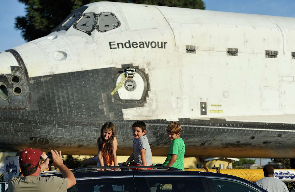 Scott Dobbins, of Manhattan Beach, takes a picture of his children, Sarah Dobbins, left, Timmy Dobbins and Will Dobbins with Space Shuttle Endeavour on Crenshaw Blvd. enroute to the California Science Center during its final journey in Los Angeles, Calif., Saturday Oct. 13, 2012.