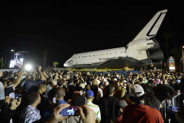 Thousands of spectators gather around the Space Shuttle Endeavour during its stops outside the Baldwin Hill Crenshaw Mall in Los Angeles, California, USA, Saturday night Oct. 13, 2012 during the two-day 'Mission 26: The Big Endeavour' trip across the city to the California Science Center where it will be put on permanent display. Photo: AP