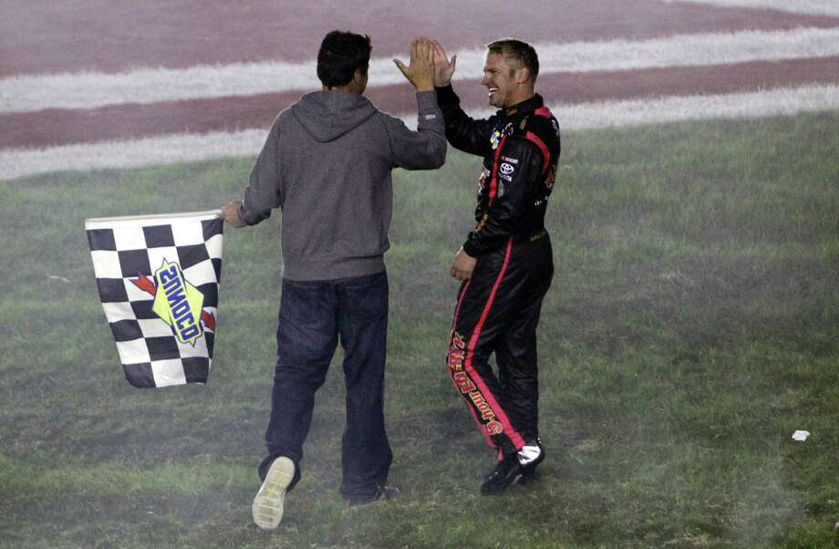 In this pool photo provided by HHP Images, Clint Bowyer, right, celebrates with team owner Michael Waltrip, left, after winning the NASCAR Bank of America 500 Sprint Cup series auto race in Concord, N.C., Saturday, Oct. 13, 2012. (AP Photo/Brian Lawdermilk, Pool) Photo: Brian Lawdermilk