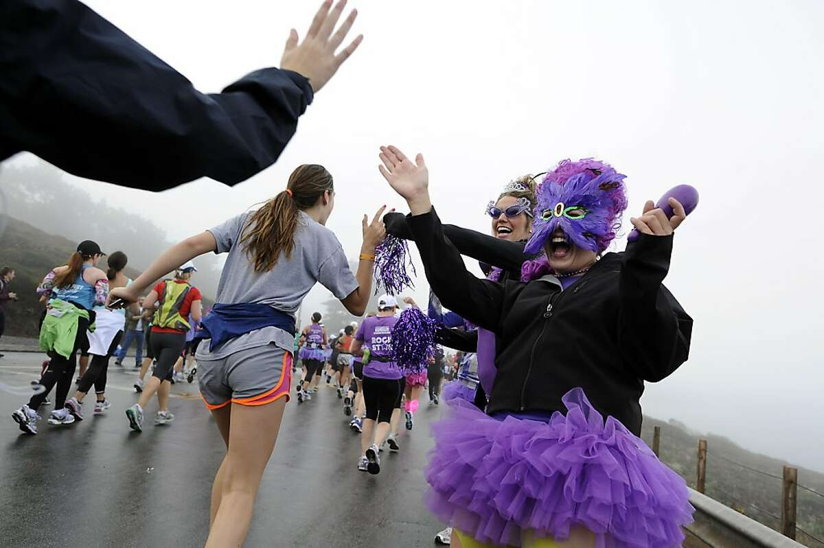 Amanda Pineiro(R) and Janet Perkins of Team in Training, part of the Leukemia and Lymphoma Society, give high-fives to runners as they pass during the 2012 Nike Women?•s Marathon & Half Marathon in San Francisco, CA on Sunday, October 14th, 2012