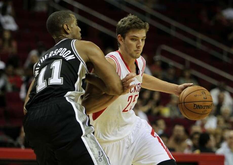 The Houston Rockets Chandler Parsons right, drives past the San Antonio Spurs Wesley Witherspoon during the first quarter of NBA preseason game action at the Toyota Center Sunday, Oct. 14, 2012, in Houston. ( James Nielsen / Chronicle ) (Chronicle)