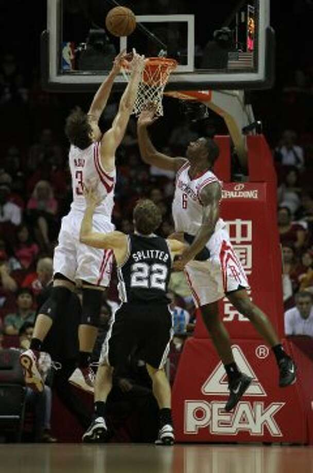The Houston Rockets Omar Asik left, and Terrence Jones right, jump for a rebound as the San Antonio Spurs Tiago Splitter looks on during the first quarter of NBA preseason game action at the Toyota Center Sunday, Oct. 14, 2012, in Houston. ( James Nielsen / Chronicle ) (Chronicle)