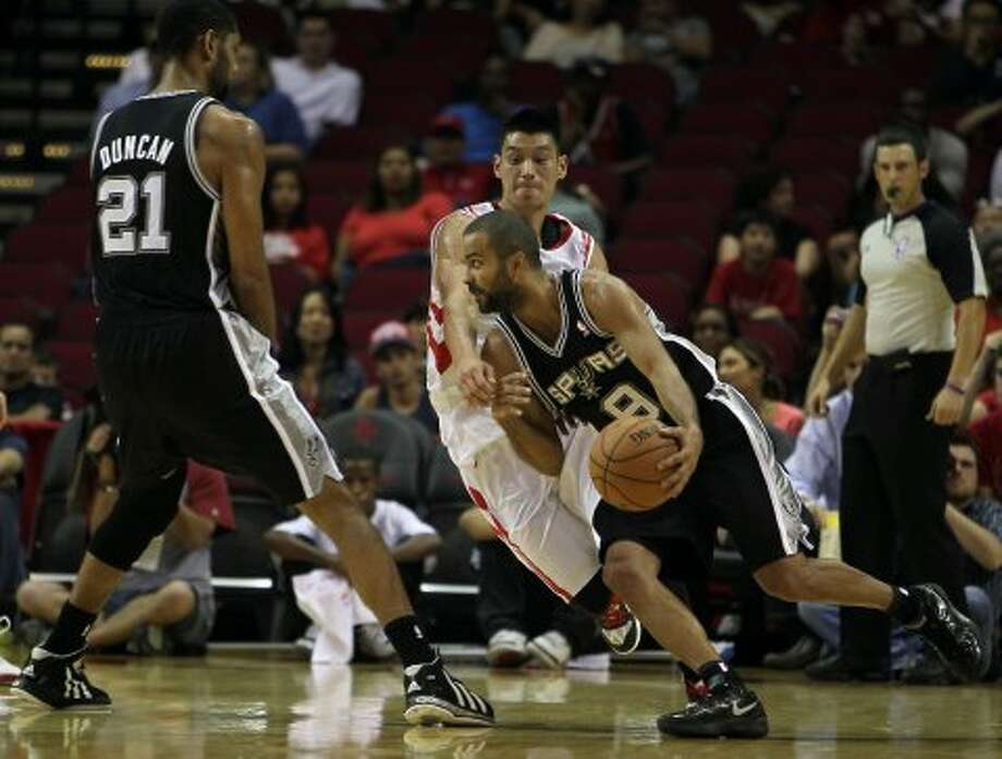 The San Antonio Spurs Tony Parker center, drives past the Houston Rockets Jeremy Lin right, as the Spurs Tim Duncan looks on during the first quarter of NBA preseason game action at the Toyota Center Sunday, Oct. 14, 2012, in Houston. ( James Nielsen / Chronicle ) (Chronicle)