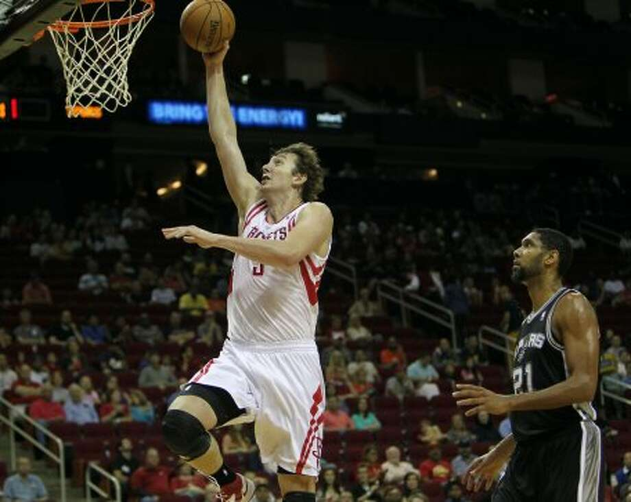 The Houston Rockets Omar Asik left, slam dunks the ball as the San Antonio Spurs tim Duncan looks on during the first quarter of NBA preseason game action at the Toyota Center Sunday, Oct. 14, 2012, in Houston. ( James Nielsen / Chronicle ) (Chronicle)