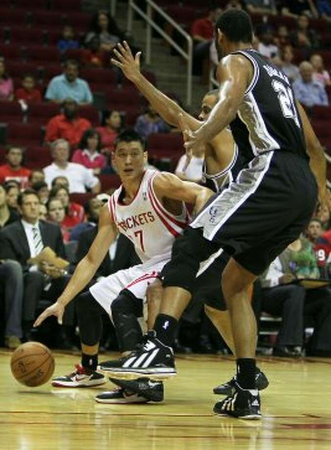 The Houston Rockets Jeremy Lin left, and the San Antonio Spurs Tony Parker center, and Tim Duncan during the first quarter of NBA preseason game action at the Toyota Center Sunday, Oct. 14, 2012, in Houston. ( James Nielsen / Chronicle ) (Chronicle)