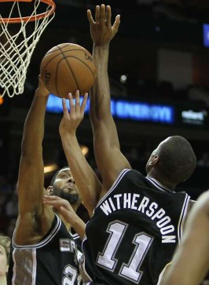 The San Antonio Spurs Tim Duncan left, and Wesley Witherspoon jump for a rebound against the Houston Rockets during the first quarter of NBA preseason game action at the Toyota Center Sunday, Oct. 14, 2012, in Houston. ( James Nielsen / Chronicle ) (Chronicle)