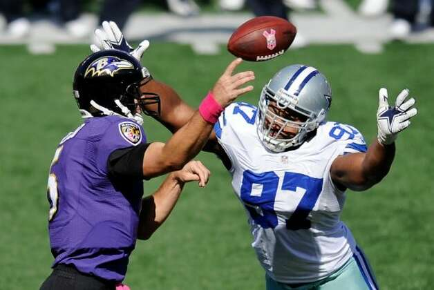 Baltimore Ravens quarterback Joe Flacco, left, throws to a receiver as he is pressured by Dallas Cowboys defensive end Jason Hatcher in the first half of an NFL football game in Baltimore, Sunday, Oct. 14, 2012. (AP Photo/Nick Wass) (Associated Press)