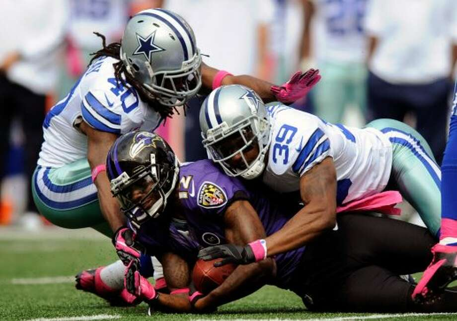 Baltimore Ravens wide receiver Jacoby Jones (12) is tackled by Dallas Cowboys defenders Danny McCray, top left, and Brandon Carr in the first half of an NFL football game in Baltimore, Sunday, Oct. 14, 2012. AP Photo/Nick Wass