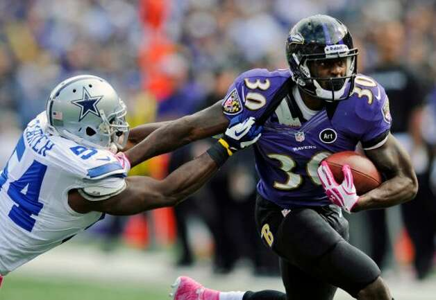 Baltimore Ravens running back Bernard Pierce, right, tries to outrun Dallas Cowboys inside linebacker Bruce Carter in the first half of an NFL football game in Baltimore, Sunday, Oct. 14, 2012. (AP Photo/Nick Wass) (Associated Press)