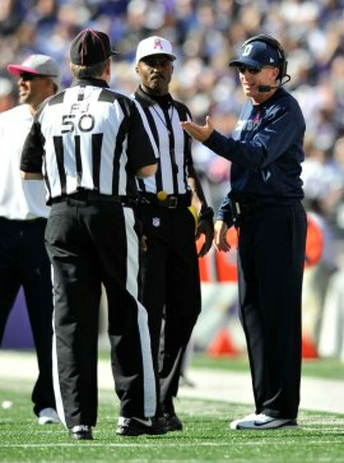 Cowboys coach Jason Garrett, right, speaks with field judge Mike Weir (50) and referee Mike Carey in the second half against the Ravens in Baltimore, Sunday, Oct. 14, 2012. (AP Photo/Gail Burton)