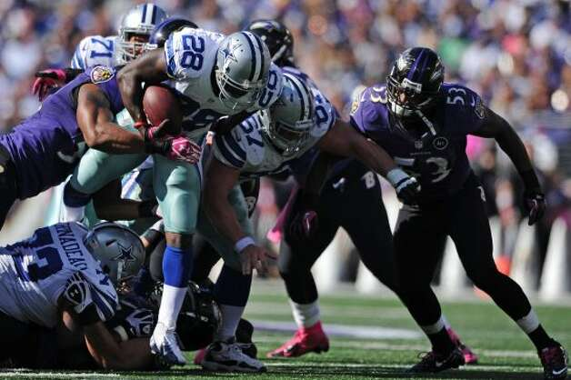 Running back Felix Jones #28 of the Dallas Cowboys breaks through a pack of Baltimore Ravens defenders in the third quarter at M&T Bank Stadium on October 14, 2012 in Baltimore, Maryland. The Baltimore Ravens won, 31-29. (Photo by Patrick Smith/Getty Images) (Getty Images)