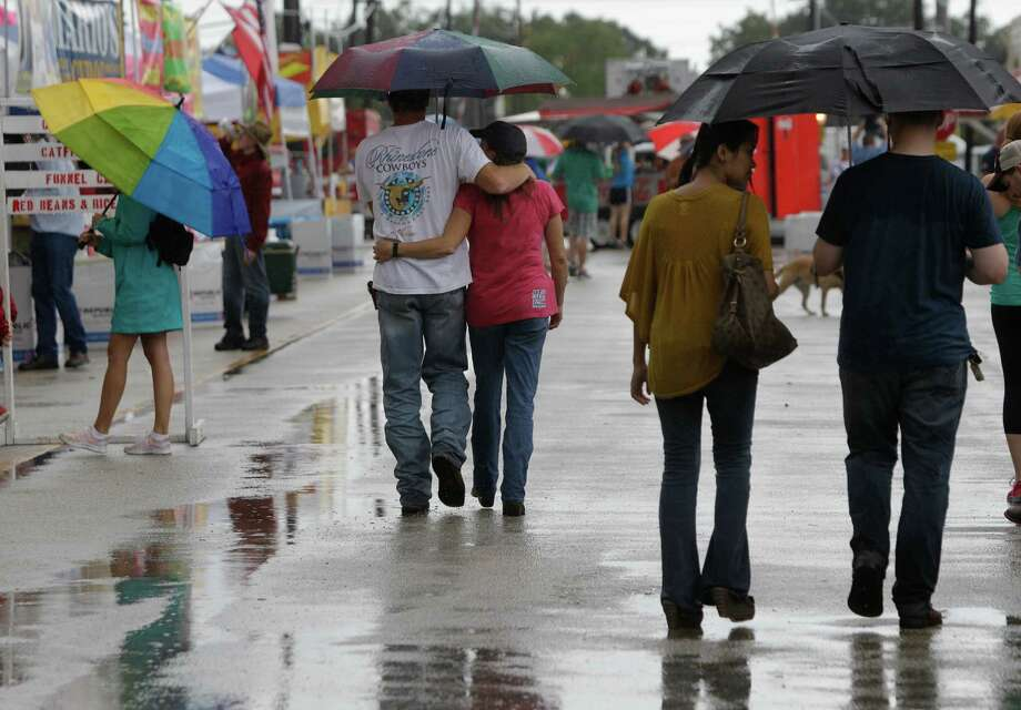 People attend 32rd Annual Katy Rice Harvest Festival, despite rain Sunday, Oct. 14, 2012, in Katy. The two day event included live entertainment, craft and food booths and a carnival. Photo: Melissa Phillip, Houston Chronicle / © 2012 Houston Chronicle