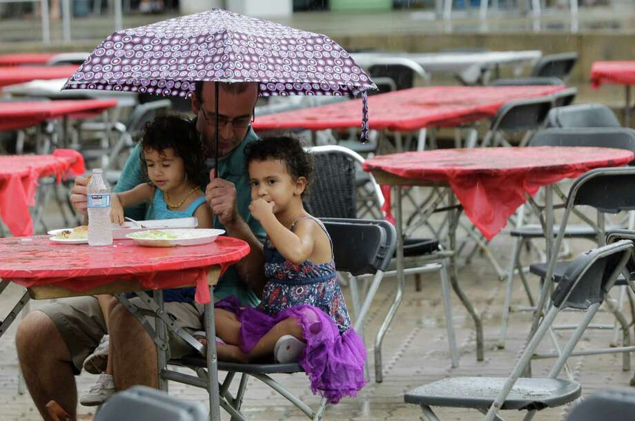 Haluk Yildirim of Austin and his daughters, Madelyn Yildirim, 2, left, and Evelyn Yildirim, 4, right, eat in the rain during the 22nd Annual Houston Turkishfest at Jones Plaza, 601 Louisiana Street, Sunday, Oct. 14, 2012, in Houston. The two day event included a Grand Bazaar of arts and crafts, music, food, and kids activities. Photo: Melissa Phillip, Houston Chronicle / © 2012 Houston Chronicle
