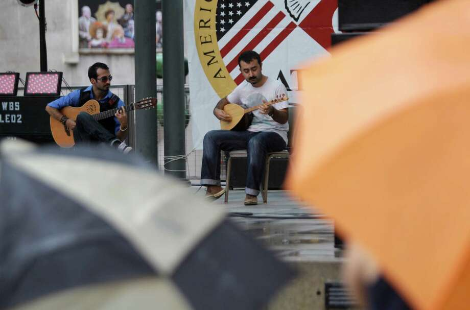 Tolga Guner, left, and Onur Gundall perform Turkish folk music during the 22nd Annual Houston Turkishfest at Jones Plaza, 601 Louisiana Street, Sunday, Oct. 14, 2012, in Houston. The two day event included a Grand Bazaar of arts and crafts, music, food, and kids activities. Photo: Melissa Phillip, Houston Chronicle / © 2012 Houston Chronicle