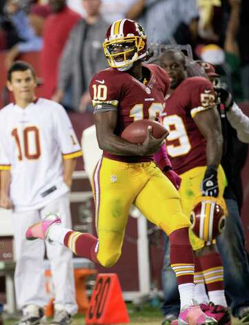 Washington Redskins quarterback Robert Griffin III (10) looks back over his shoulder as he sprints down the sideline for a touchdown against the Minnesota Vikings in the second half at FedEx Field in Landover, MD, Sunday, October 14, 2012. Washington defeated Minnesota 38-26. (Harry E. Walker/MCT) Photo: Harry E. Walker, McClatchy-Tribune News Service / McClatchy-Tribune Photo Service 2012