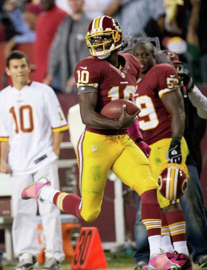 Washington Redskins quarterback Robert Griffin III (10) looks back over his shoulder as he sprints d