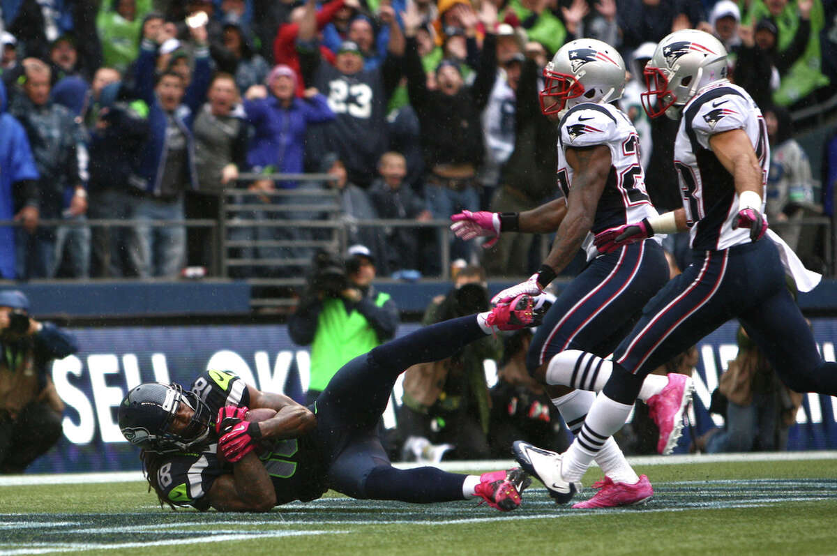 Seattle Seahawks player Sidney Rice pulls in a final touchdown as he is pursued by New England Patriots players Nate Ebner (43) and Tavon Wilson (27) in the fourth quarter of an NFL game on Sunday, October 14, 2012 at CenturyLink Field in Seattle. The Hawks won 24 to 23.
