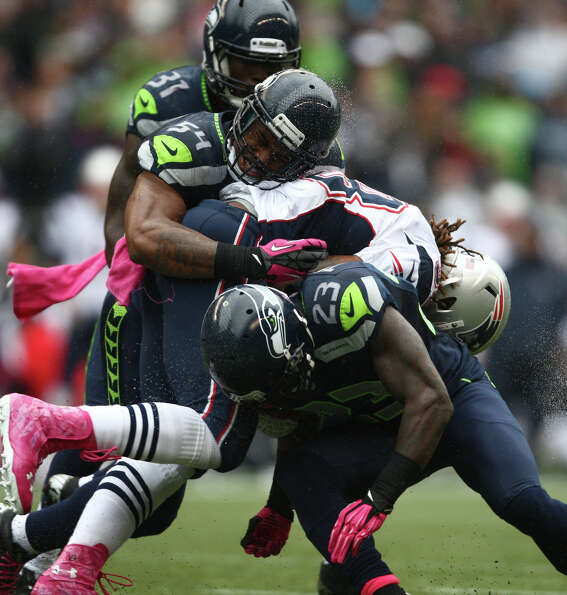 Seattle Seahawks players Kam Chancellor (31), Bobby Wagner (54) and Marcus Trufant (23) crush  New E