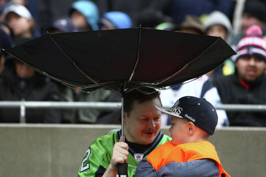 Seattle Seahawks fans try to keep dry during a downpour during a game against the New England Patriots on Sunday, October 14, 2012 at CenturyLink Field in Seattle. The Hawks beat the Patriots 24 to 23. Photo: JOSHUA TRUJILLO / SEATTLEPI.COM