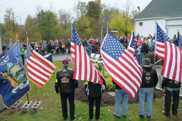 Members of the Patriot Guard Riders hold flags  during a ceremony to celebrate the naming of the Route 20 Bridge in the Town of Nassau on Sunday, Oct. 14, 2012.  The bridge was named the Staff Sergeant Derek Farley Memorial Bridge.  Derek Farley was an Army explosives ordnance disposal technician who was deployed in 2009 as team leader to Afghanistan with the 702nd EOD Company.  Farley died in Afghanistan on August 17, 2010.   (Paul Buckowski / Times Union) Photo: Paul Buckowski