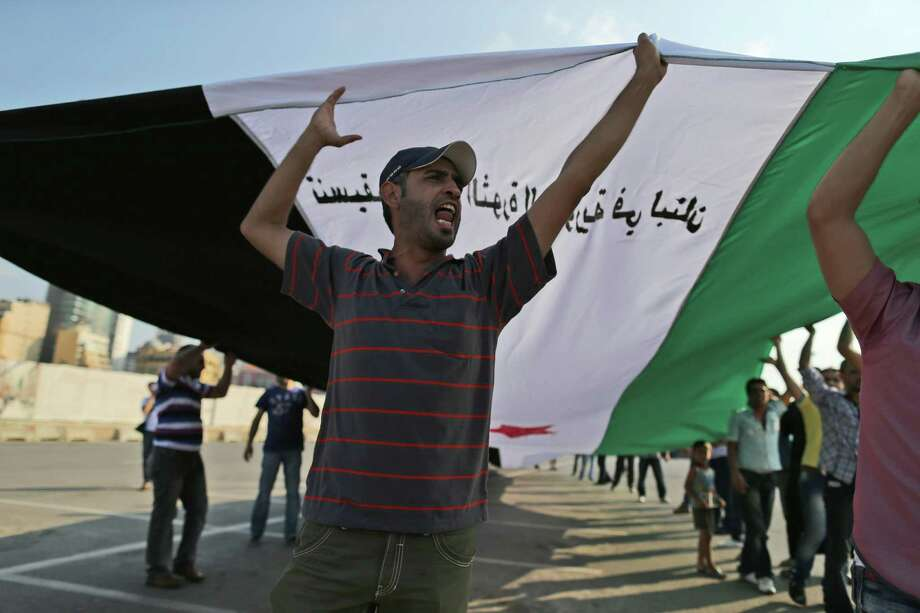 An anti-Syrian regime protester carries a large Syrian revolutionary flag during a demonstration in downtown of Beirut, Lebanon, Sunday, Oct. 14, 2012. Assir, a strong critic of Hezbollah leader Hasan Nasrallah and Syrian President Bashar Assad, has organized multiple protests over the past year in a bid to increase support for the Syrian uprising and mount an offensive against Nasrallah for openly supporting Assad's regime. (AP Photo/Hassan Ammar) Photo: Hassan Ammar