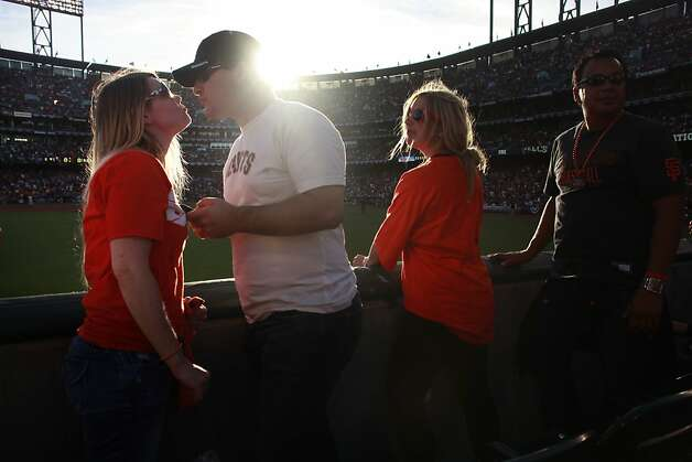 Heather and Gabriel Tait, of Santa Rosa, steal a kiss in the bleachers at the San Francisco Giants play the St. Louis Cardinals in NLCS Game 1 on Sunday Oct. 14, 2012 in San Francisco, Calif. Photo: Mike Kepka, The Chronicle