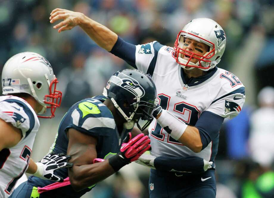 New England Patriots quarterback Tom Brady passes under pressure from Seattle Seahawks' Chris Clemons, center, in the first half of an NFL football game, Sunday, Oct. 14, 2012, in Seattle. (AP Photo/John Froschauer) Photo: John Froschauer