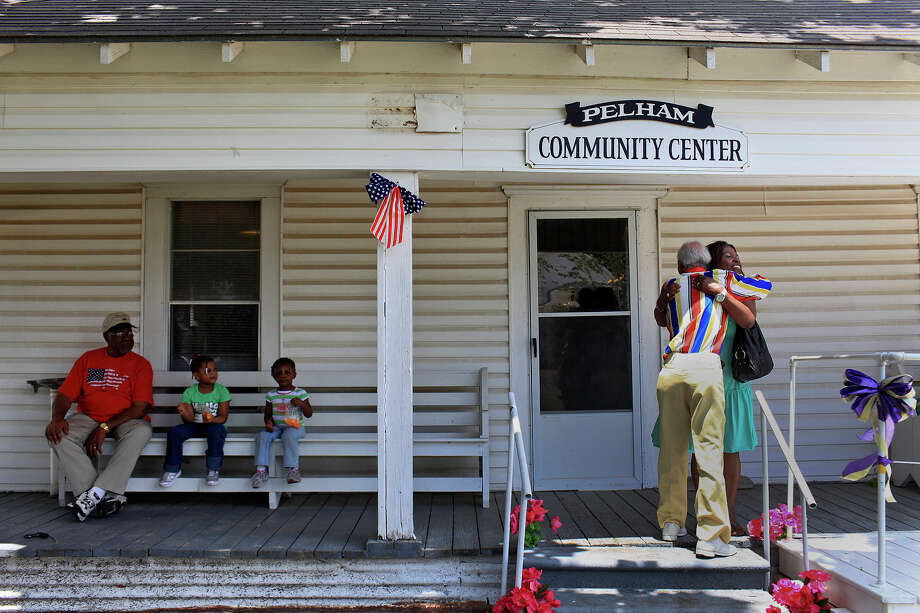 Lottye Burns, of Cedar Hill, whose husband grew up in Pelham, embraces Pelham native Elvis Caruthers, 90, at the conclusion of the Memorial Day events at the Pelham Community Center on Sunday, May 27, 2012. At left, Pelham resident Burtis Robinson, sits with Sydney Chandler, 5, and Chloe Chandler, 3, of Grand Prairie. Photo: Lisa Krantz, Express-News / © 2012 San Antonio Express-News