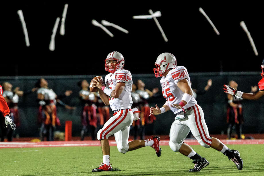 "Rifles fly in the background as Judson quarterback Jonathan Garcia, with Gerardo Zacarias giving protection, looks for a receiver during thei rgame with Wagner at Rutledge Stadium on Oct. 12, 2012.  Judson won the ""Hammer Bowl"" 30-0.    MARVIN PFEIFFER/ mpfeiffer@express-news.net Photo: MARVIN PFEIFFER, Express-News / Express-News 2012"