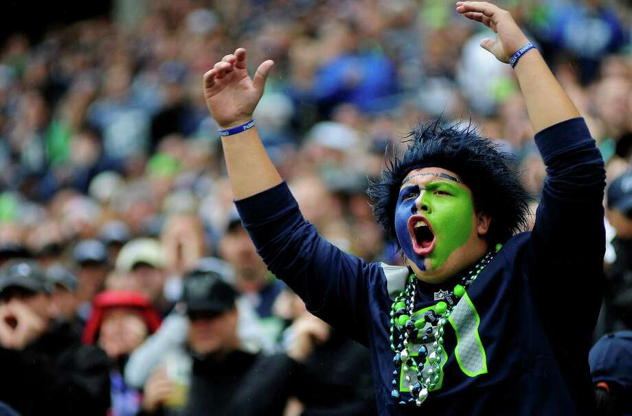 Tyler McCaulley raises his arms and cheers as the Seahawks prepare for a play during their game against the Patriots at CenturyLink Field on Sunday, October 14, 2012. The Seahawks took the game 24-23. Photo: LINDSEY WASSON / SEATTLEPI.COM