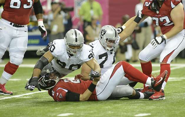Atlanta Falcons quarterback Matt Ryan (2) goes down after a pass as Oakland Raiders defensive tackle Desmond Bryant (90) and Oakland Raiders defensive end Matt Shaughnessy (77) defend during the first half of an NFL football game, Sunday, Oct. 14, 2012, in Atlanta. The Raiders caught a roughing the passer call. (AP Photo/Billy Weeks) Photo: Billy Weeks, Associated Press