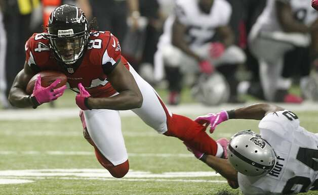 Atlanta Falcons wide receiver Roddy White (84) makes the catch as Oakland Raiders cornerback Michael Huff (24) defends during the first half of an NFL football game, Sunday, Oct. 14, 2012, in Atlanta. (AP Photo/John Bazemore) Photo: John Bazemore, Associated Press