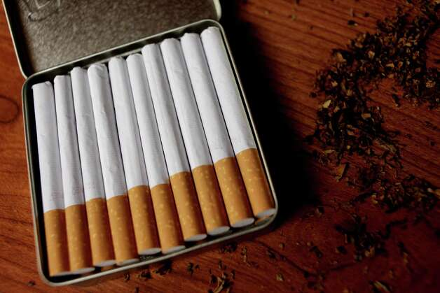 "In this Sunday, Nov. 20, 2011 photo, cigarettes made by a customer lie next to loose tobacco at Island Smokes in New York. There is no place in the U.S. where it costs more to smoke than New York City, where the state and local taxes alone will set you back $6.46 per pack. Yet, smokers who visit Island Smokes, a ""roll-your-own"" tobacco shop in Manhattan's Chinatown, can walk out with an entire carton of cigarettes for an advertised price of $39.95, thanks to a tax loophole that officials in several states are now trying to close. (AP Photo/Seth Wenig) Photo: Seth Wenig"