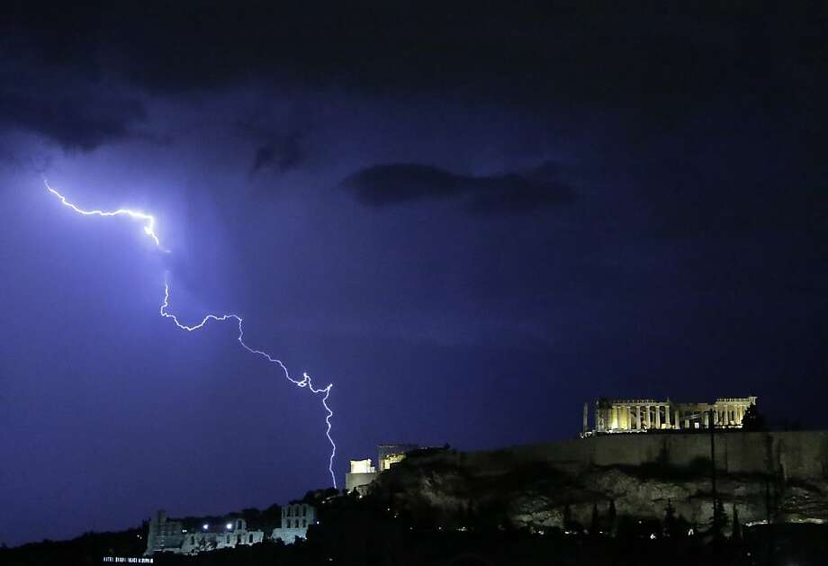 Lightening illuminates the ancient Parthenon temple atop the Acropolis hill in Athens on Sunday Oct. 14, 2012. Greece is inching towards an agreement with its international debt inspectors as they struggle to hammer out the details of euro13.5 billion ($17.5 billion) in austerity measures for the next two years, a package essential for Greece to receive the next installment of its vital bailout funds. (AP Photo/Dimitri Messinis) Photo: Dimitri Messinis, Associated Press