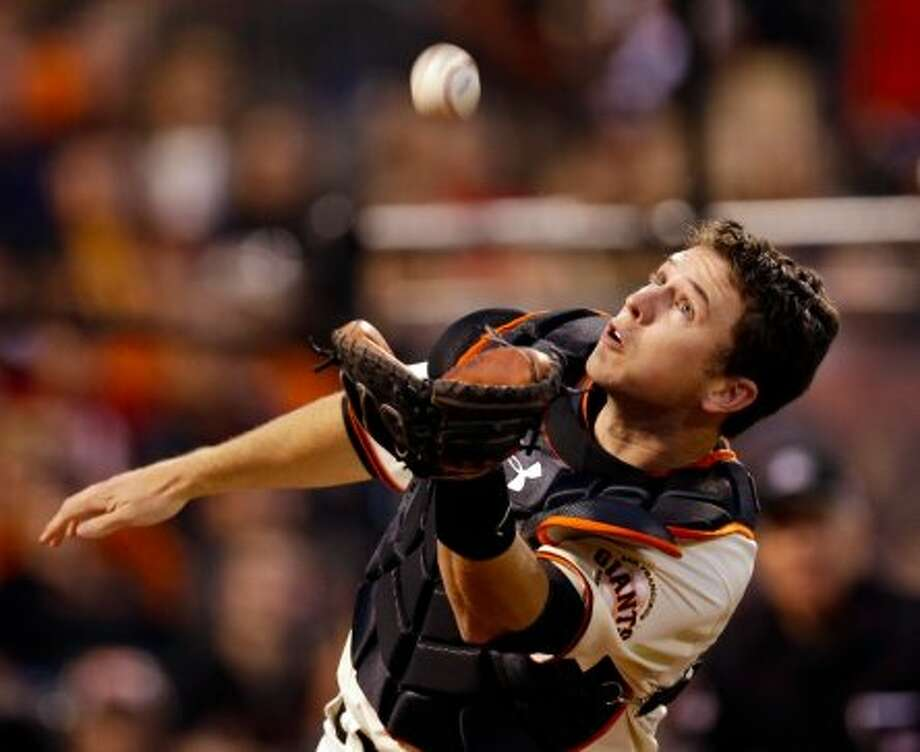 San Francisco Giants catcher Buster Posey makes a diving catch on a foul ball hit by St. Louis Cardinals' Matt Holliday during the fourth inning of Game 1 of baseball's National League championship series Sunday, Oct. 14, 2012, in San Francisco. (AP Photo/David J. Phillip) (David J. Phillip / Associated Press)