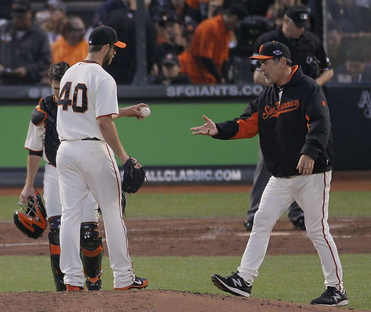 Giants' pitcher Madison Bumgarner hands the ball to Bruce Bochy in the fourth inning during game 1 of the NLCS at AT&T Park on Sunday, Oct. 14, 2012 in San Francisco, Calif.