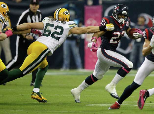 Houston Texans running back Arian Foster (23) tries to run around Green Bay Packers outside linebacker Clay Matthews (52) during the second quarter at Reliant Stadium on Sunday, Oct. 14, 2012, in Houston. Photo: Brett Coomer, Houston Chronicle / © 2012  Houston Chronicle