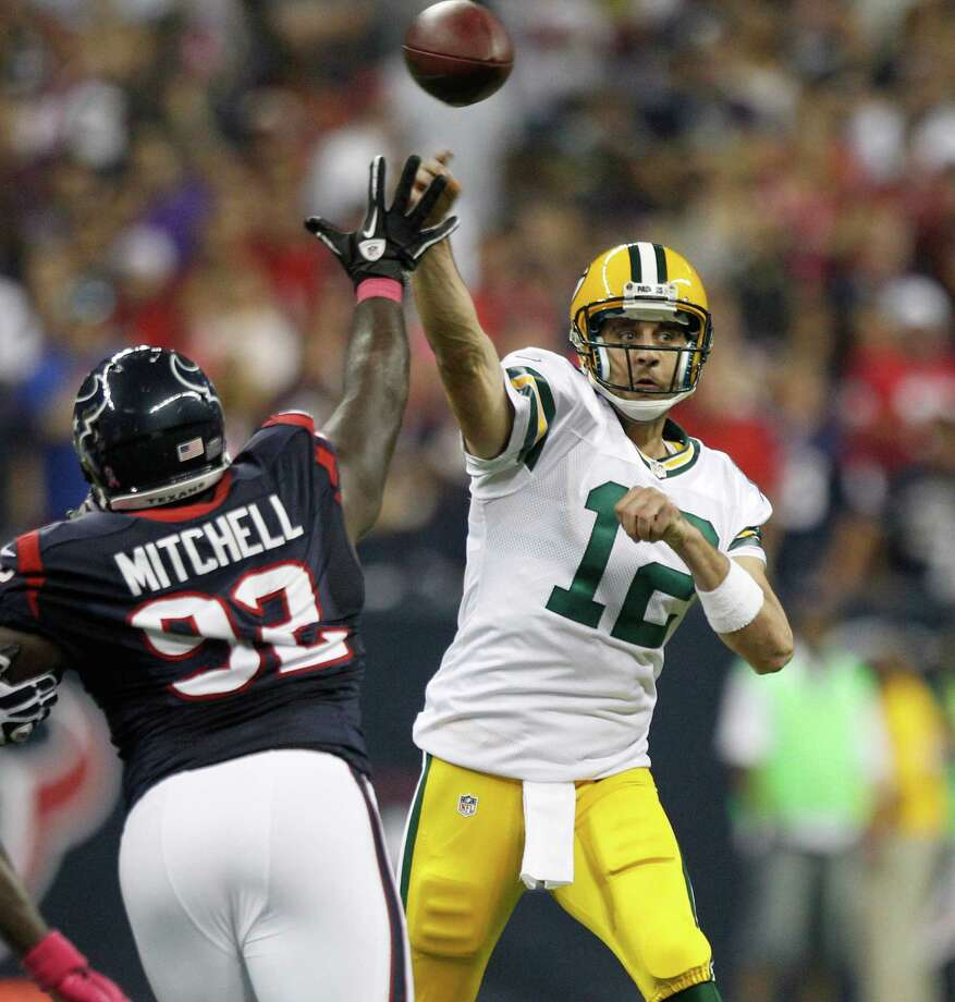 Green Bay Packers quarterback Aaron Rodgers (12) makes a pass over Houston Texans defensive tackle Earl Mitchell (92) during the first quarter at Reliant Stadium on Sunday, Oct. 14, 2012, in Houston. Photo: Brett Coomer, Houston Chronicle / © 2012  Houston Chronicle