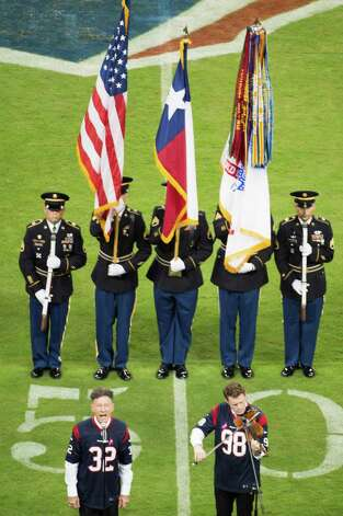 Lyle Lovett sings the national anthem before the Houston Texans game against the Green Bay Packers at Reliant Stadium on Sunday, Oct. 14, 2012, in Houston. Photo: Smiley N. Pool, Houston Chronicle / © 2012  Houston Chronicle