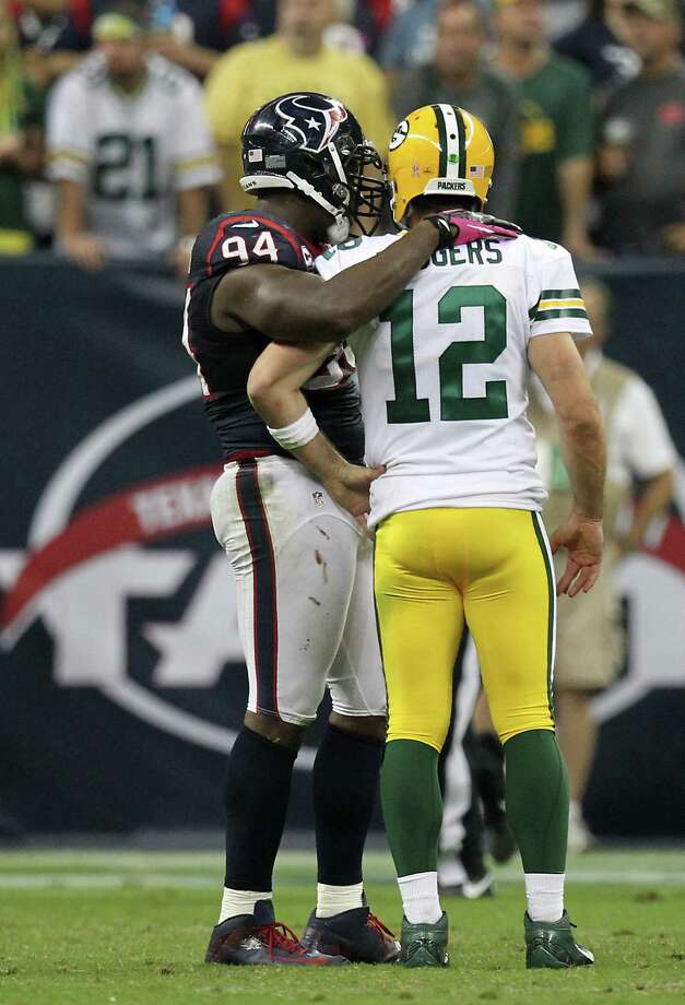 Houston Texans defensive end Antonio Smith (94) puts his arm around Green Bay Packers quarterback Aaron Rodgers (12) during the third quarter at Reliant Stadium, Sunday, Oct. 14, 2012, in Houston. Photo: Nick De La Torre, Houston Chronicle / © 2012  Houston Chronicle