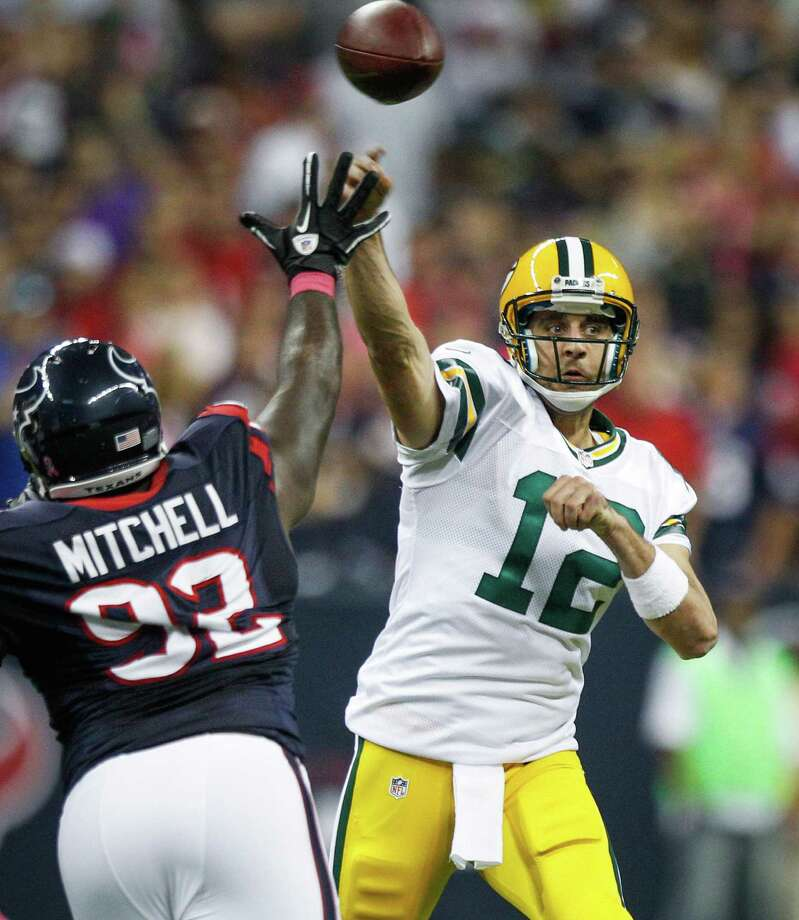 Packers quarterback Aaron Rodgers (12) makes a pass over Texans defensive tackle Earl Mitchell (92) during the first quarter. Photo: Brett Coomer, Houston Chronicle / © 2012  Houston Chronicle