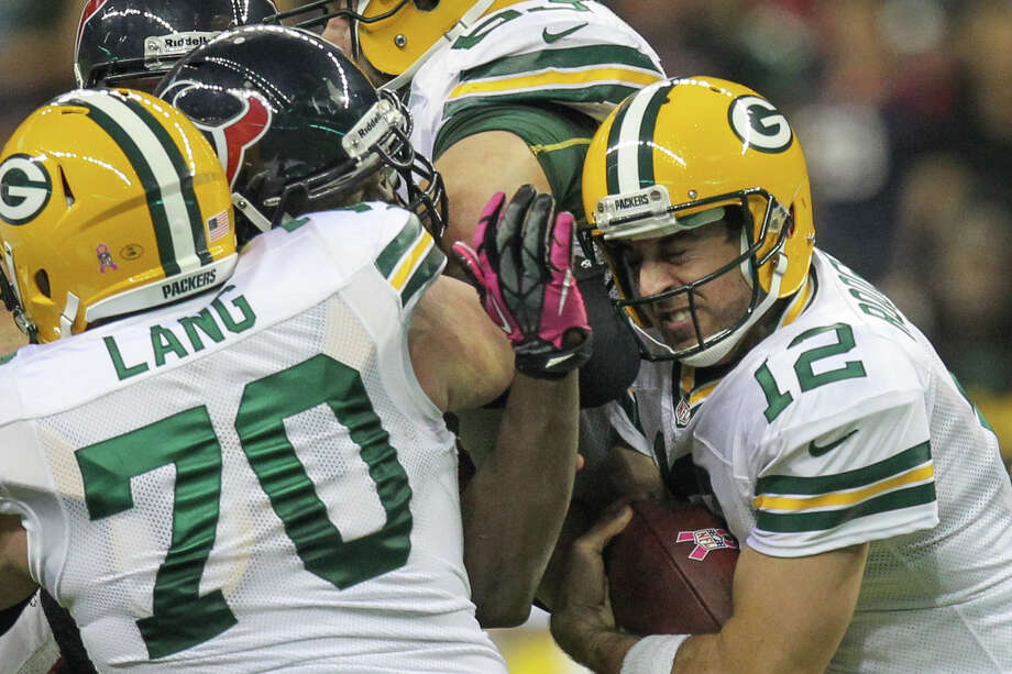 Packers quarterback Aaron Rodgers (12) fights for yardage against the Texans defense during the second quarter. Photo: Nick De La Torre, Houston Chronicle / © 2012  Houston Chronicle
