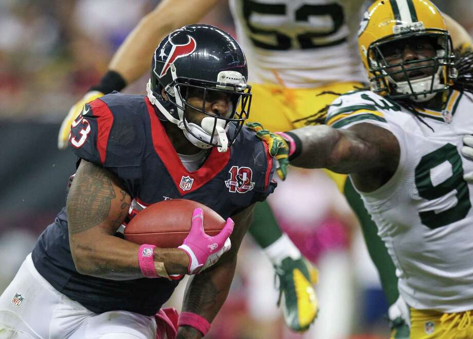 Texans running back Arian Foster (23) scores on a 1-yard touchdown run as he gets past Green Bay outside linebacker Erik Walden (93) during the second quarter. Photo: Nick De La Torre, Houston Chronicle / © 2012  Houston Chronicle