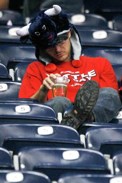 A Texans fans sits in the stands with his head down during the fourth quarter.