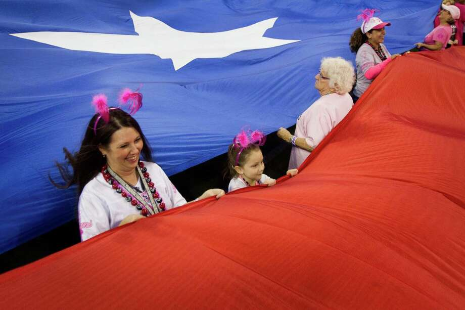Kristie Schoppe, left, Jaclyn Vandiver, center, and Joan Lee hold the Texas flag during pre-game ceremonies before the game. Photo: Brett Coomer, Houston Chronicle / © 2012  Houston Chronicle