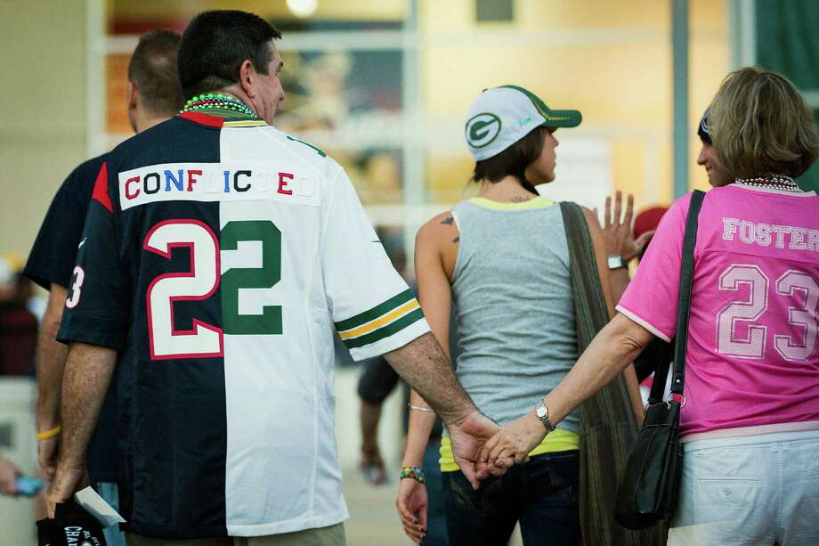"A fan wears a jersey made of a Houston Texans and Green Bay Packers jersey sewn together with the word ""conflicted"" written across the back as he arrives at Reliant Stadium for the Packers game against the Texans. Photo: Smiley N. Pool, Houston Chronicle / © 2012  Houston Chronicle"