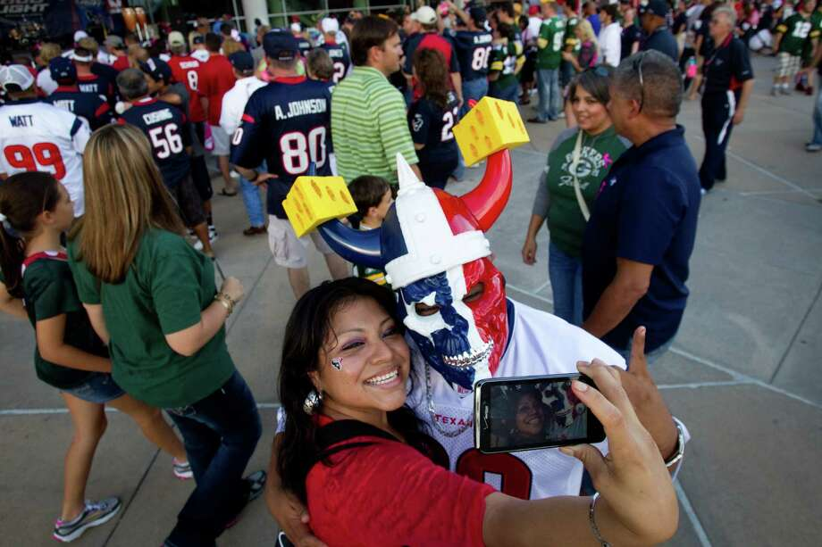 Texans fans Letty Vera, left, and her brother Mike Batalla pose for a picture on her phone before the Texans game against the Green Bay Packers. Photo: Brett Coomer, Houston Chronicle / © 2012  Houston Chronicle